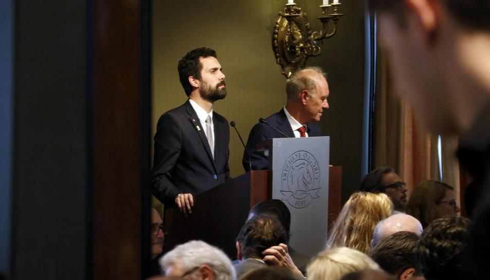 El president del Parlament, Roger Torrent, escolta les intervencions d'un col·loqui al Círculo Ecuestre amb el Cercle de Directius de Parla Alemanya, reflectit en un mirall al costat del seu president, Albert Peters