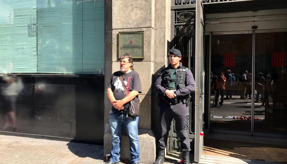 Imatge de Jordi Pesarrodona davant de Governació amb un nas de pallasso al costat d'un Guàrdia Civil.