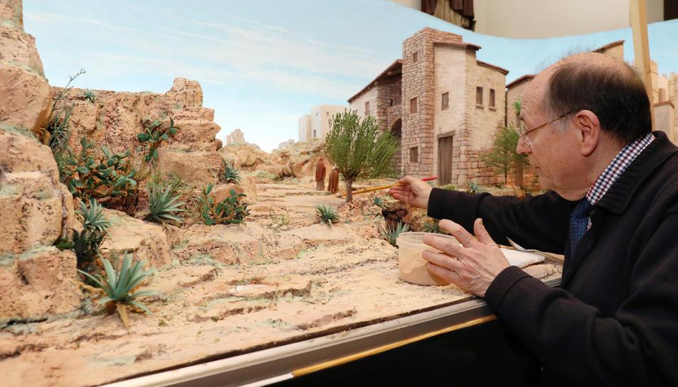 Josep Puig retoca amb un pinzell un camí que pertany a un dels espais del diorama.