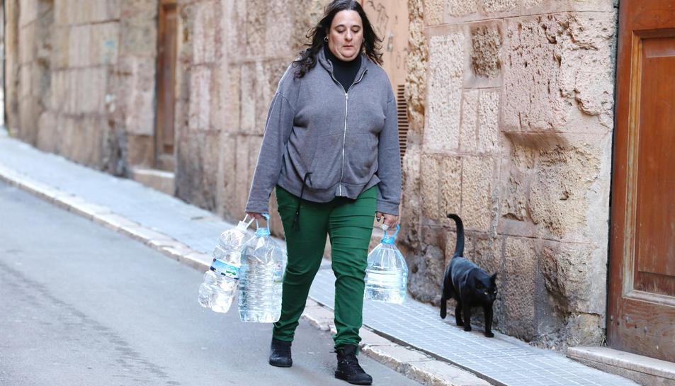 L'Elisabet carrega quatre garrafes plenes d'aigua mentre camina fins a casa seva.