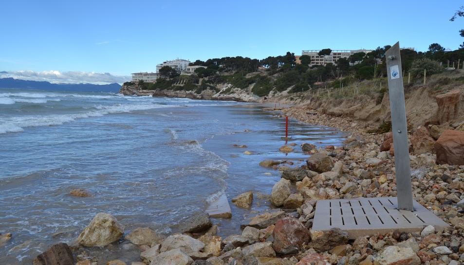 Una dutxa a la platja Llarga de Salou que està tocant al mar i, al fons, es visualitzen els pocs metres d'arena que queden.