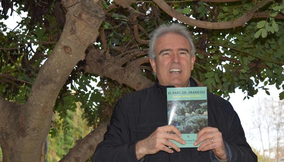 Raül Font-Quer mostra el seu llibre en un entorn dominat per la presència de garrofers.