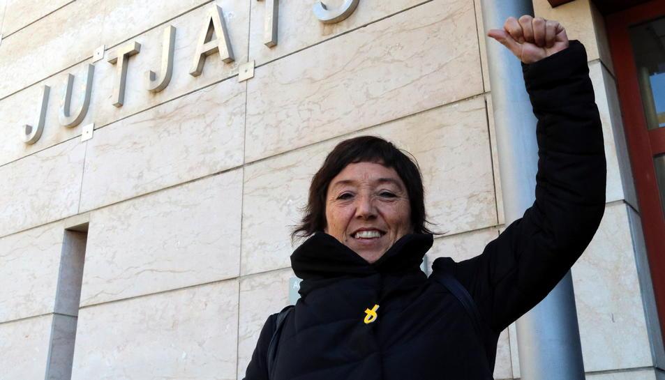 Pla mig de la regidora de la CUP de Reus, Mariona Quadrada, sortint dels jutjats de Reus, on ha hagut de comparèixer per un suposat delicte d'odi, somrient i amb el puny alçat. Imatge del 22 de març del 2018