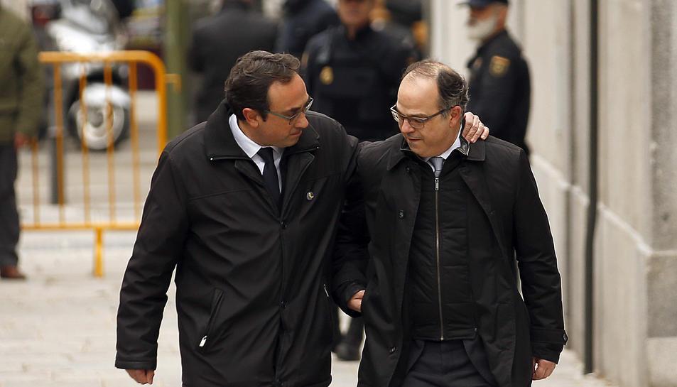 El diputat de Junts per Catalunya Josep Rull agafa per l'espatlla al candidat a la investidura i també diputat de JxCAT, Jordi Turull, abans d'entrar a la seu del Tribunal Suprem.
