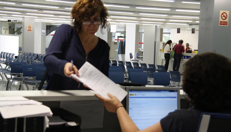 Una dona entregant la declaració de la renda a una oficina de l'Agència Tributària espanyola