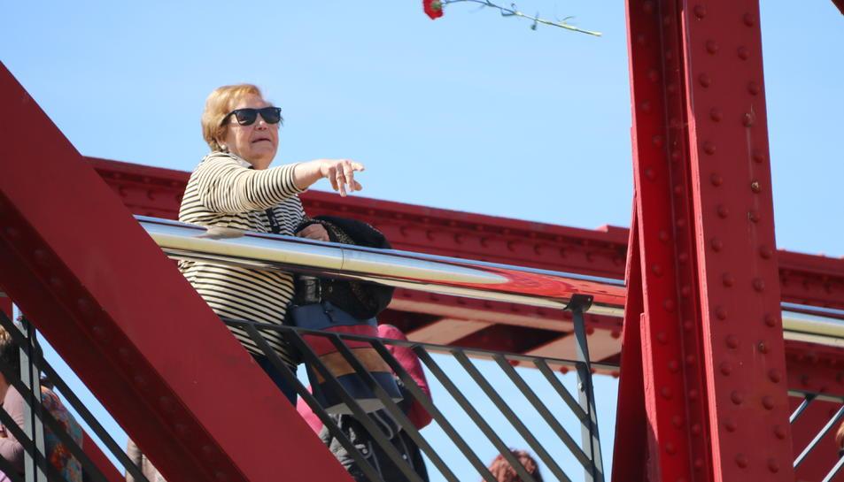 Pla mig d'una dona llençant un clavell al riu des del Pont Roig de Tortosa en l'homenatge a les víctimes de la Guerra Civil.