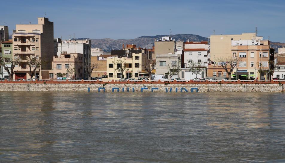 Lletres de la pintada 'El riu es vida' a Tortosa parcialment cobertes per l'aigua.