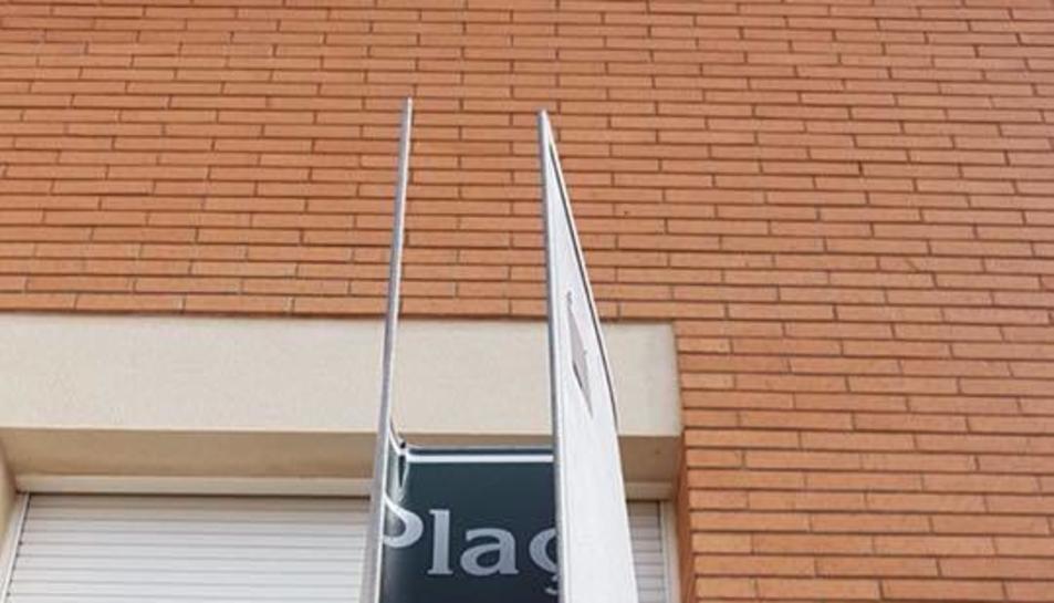 Imatge de la placa de la plaça 1 d'Octubre completament doblegada.