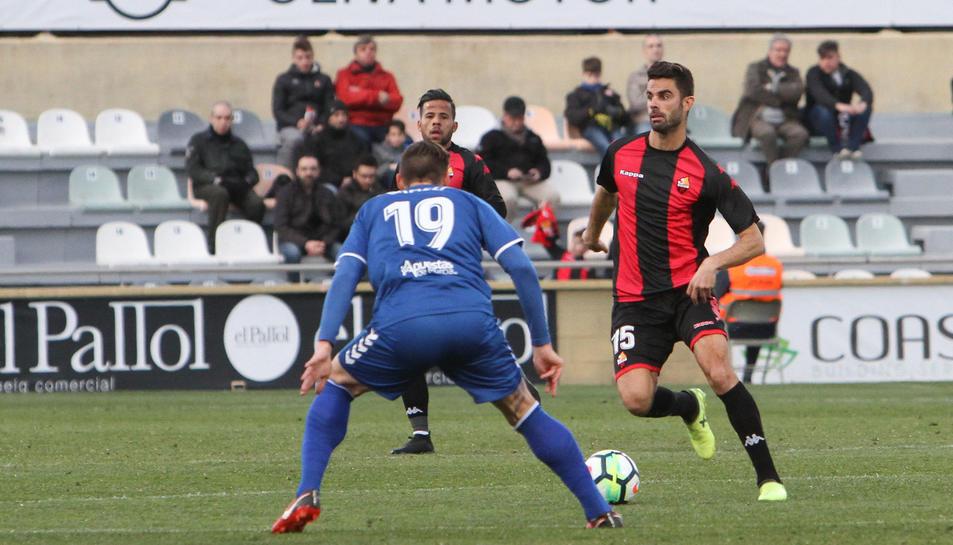 Domínguez intenta superar un rival mentre Ledes, darrera, observa l'acció.