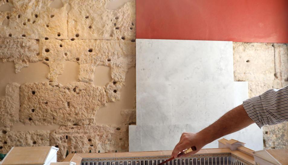 Muñoz mostra sobre una maqueta el lloc exacte del mur i, al darrere, carreus i plaques de marbre.