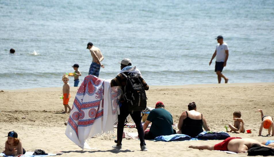 Pla sencer d'un venedor ambulant, desplegant una de les teles que ven, entre diversos banyistes a la platja de la Pineda. Imatge del 9 de maig del 2018