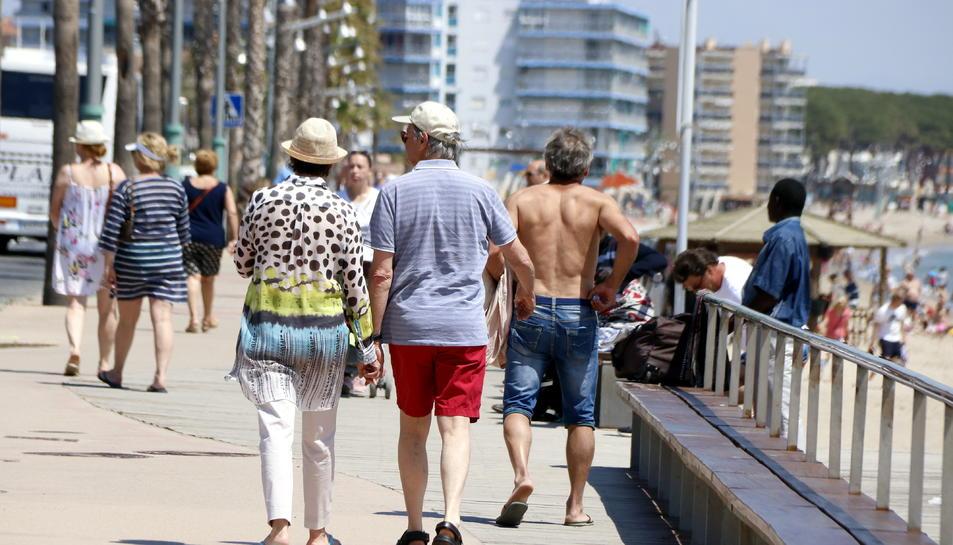 Pla general de diversos turistes passejant pel passeig marítim de la platja de la Pineda, a Vila-seca (Tarragonès),el 9 de maig del 2018