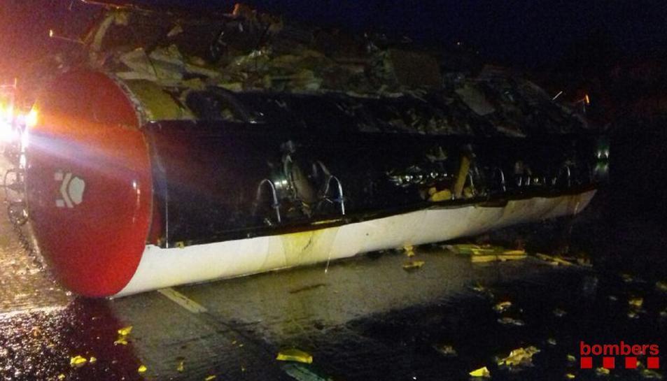 Imatge cedida pels Bombers d'una cisterna de camió bolcada després d'un accident a la N-340, a Alcanar (Montsià), el 9 de maig del 2018. Pla general