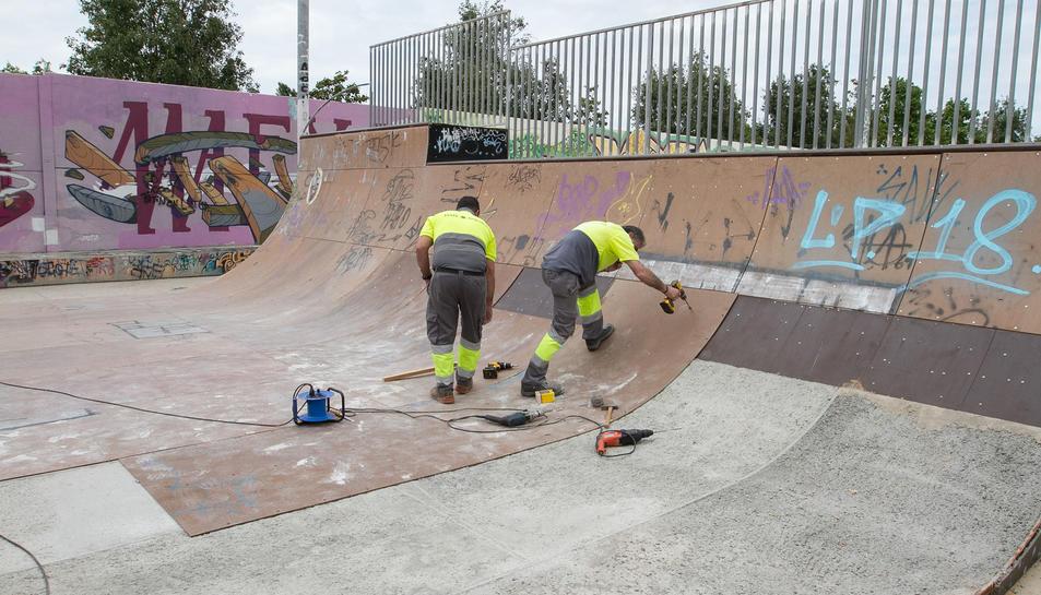 Operaris treballen per recuperar la superfície del 'half-pipe' del parc.