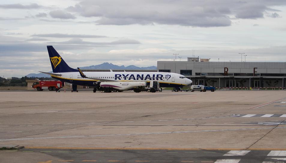 Pla general d'un avió de Ryanair al costat de la terminal de l'Aeroport de Reus.