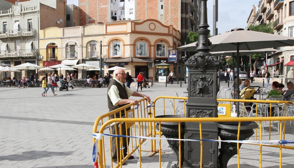 Una persona observa al detall la font que s'ha instal·lat a la plaça Corsini.