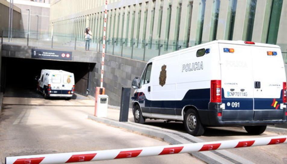 Pla mitjà des de darrere de dues furgonetes de la policia espanyola entrant al parking subterrani de la Ciutat de la Justícia, el 25-5-18.