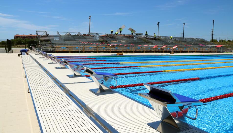 Pla obert de la piscina dels Jocs Mediterranis de Tarragona 2018, amb operaris treballant i els saltadors en primer terme. Imatge del 14 de juny del 2018