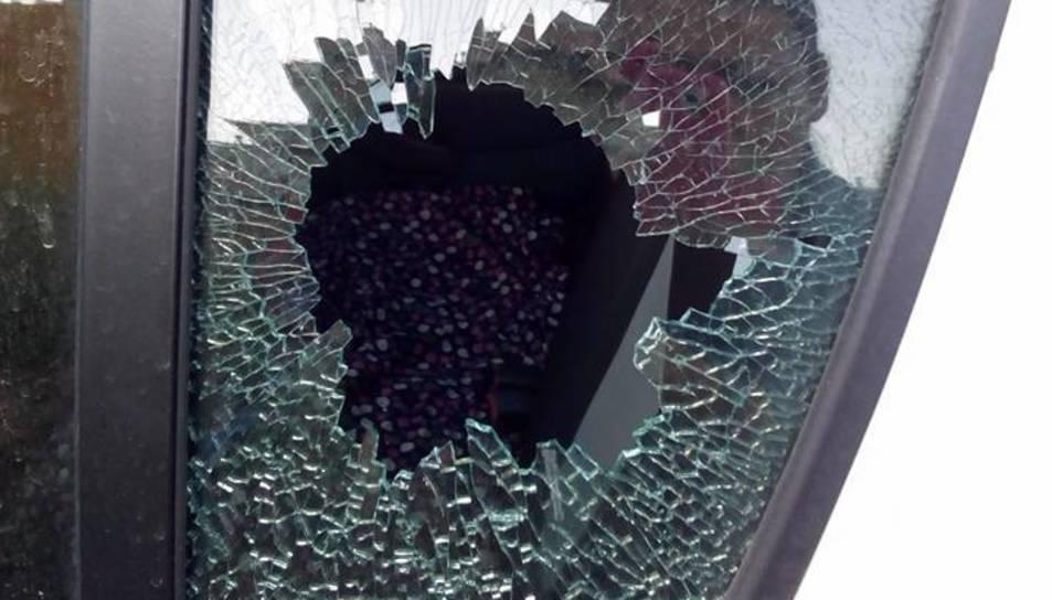 Imatge d'un dels cotxes afectats, amb una finestra trencada.