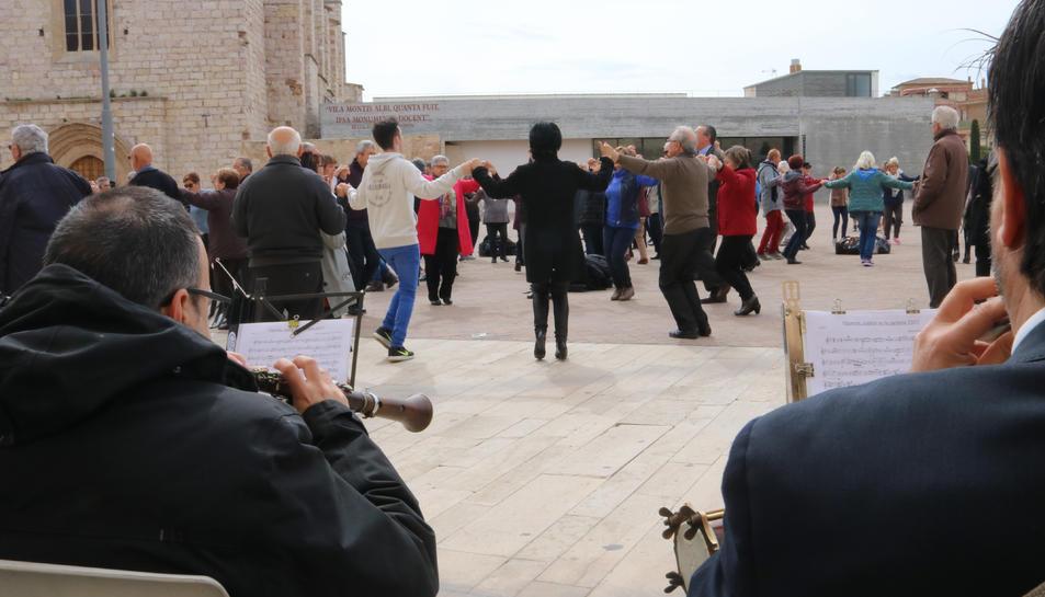 Diverses persones ballant sardana a Montblanc i dos músics de la cobla.