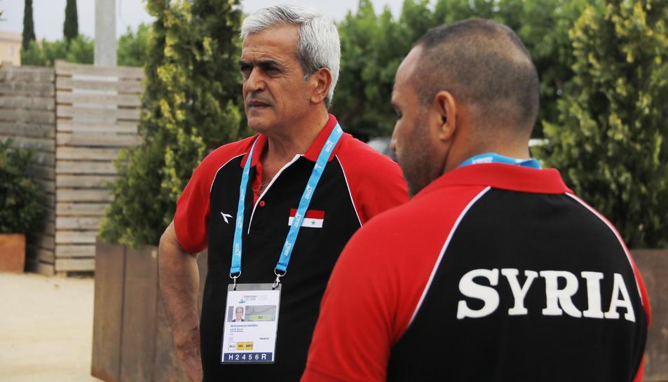 El cap de missió de la delegació de Síria als Jocs Mediterranis, Mohammad Harba. En primer pla, un altre membre de la delegació siriana amb la samarreta amb el nom del país.