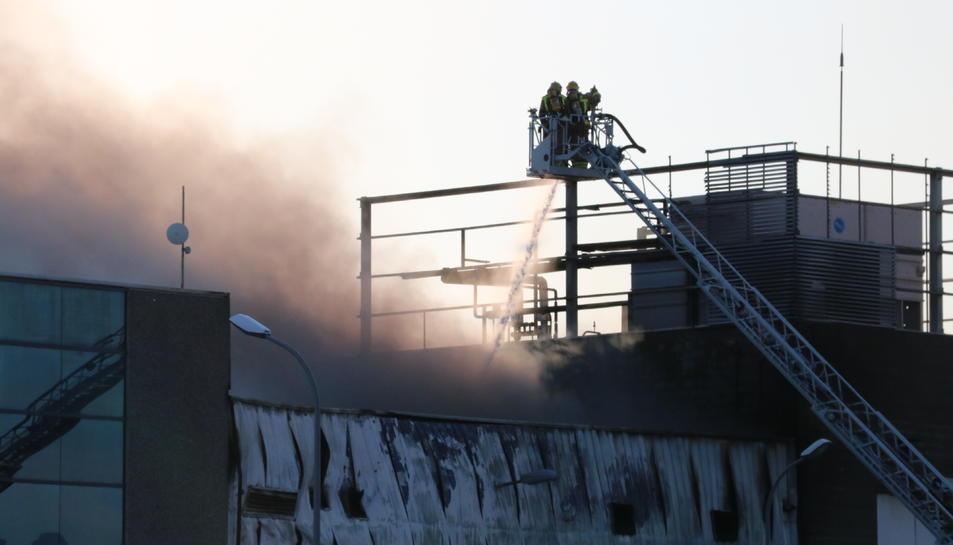 Un equip de bombers ataca les flames d'una nau del grup Balfegó incendiada el 22 de juny.