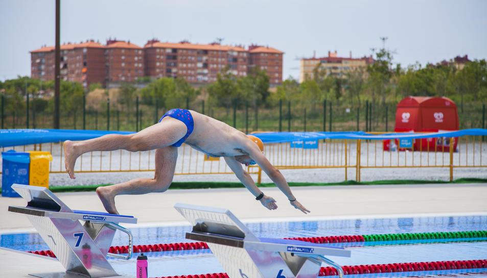 Un nedador es llença a la piscina, ja sense la grada mòbil que hi va haver durant els Jocs i que permet veure, al fons, Campclar.