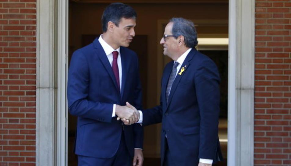 El president de la Generalitat, Quim Torra, i el president del govern espanyol, Pedro Sánchez, encaixen les mans a les portes del palau de la Moncloa.