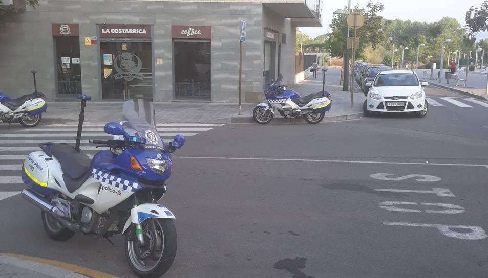 Una moto de la Guàrdia Urbana, aparcada en un lloc prohibit davant d'una cafeteria.