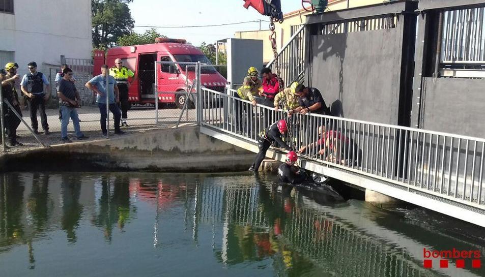Els bombers ajudant a treure el cotxe del canal