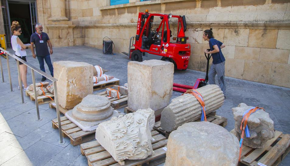 Un operari es disposa a traslladar peces fins a una furgoneta, davant l'atenta mirada de personal vinculat al museu.