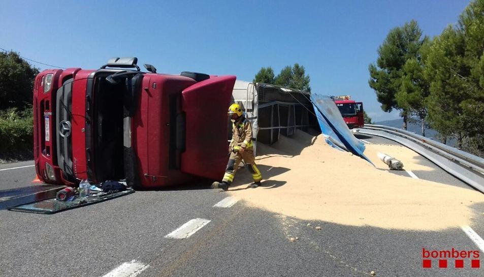La càrrega del vehicle, que transportava cereals, ha quedat estesa a la via.