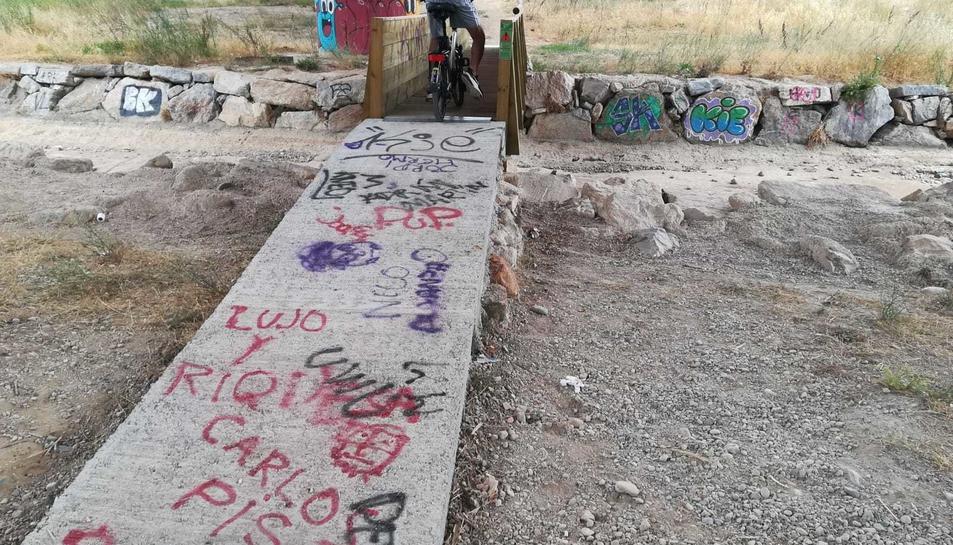 La rampa d'accés al pontet de fusta i algunes zones ja estan plenes de pintades.