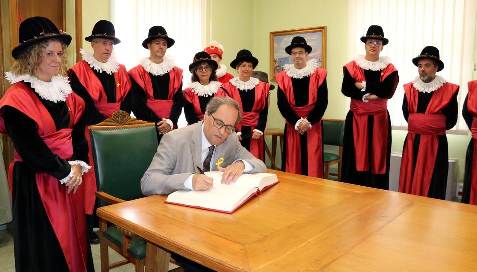 El president Quim Torra, signant el llibre d'honor a l'Ajuntament de Tortosa, amb l'alcaldessa Meritxell Roigé al costat, durant una visita per la Festa del Renaixement.