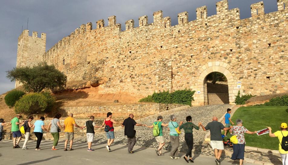 Diverses persones ballant una sardana tot encerclant la muralla de Montblanc.