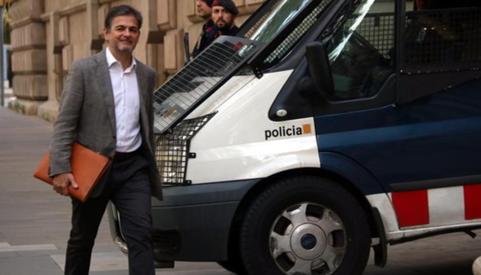 Pla mitjà d'Oriol Pujol arribant a l'Audiència de Barcelona, passant per davant d'un furgó dels Mossos.