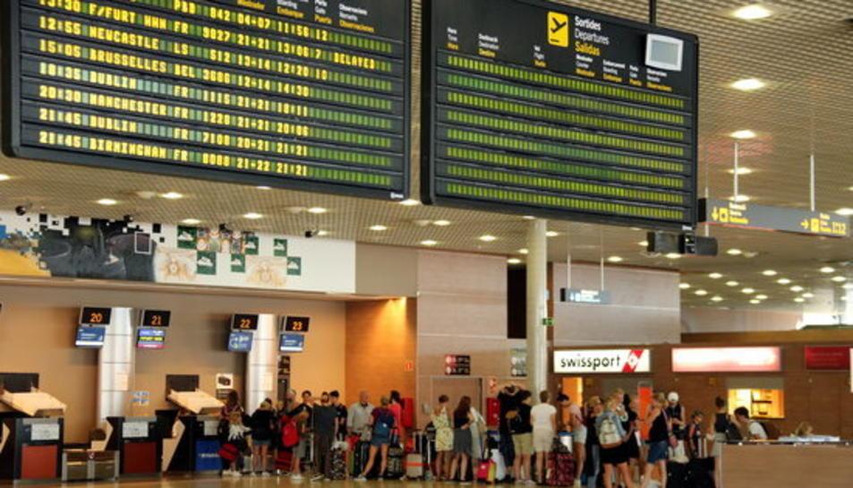 Pantalla indicant un retard en un vol de Ryanair a Frankfurt i cues de fons a l'Aeroport de Reus.