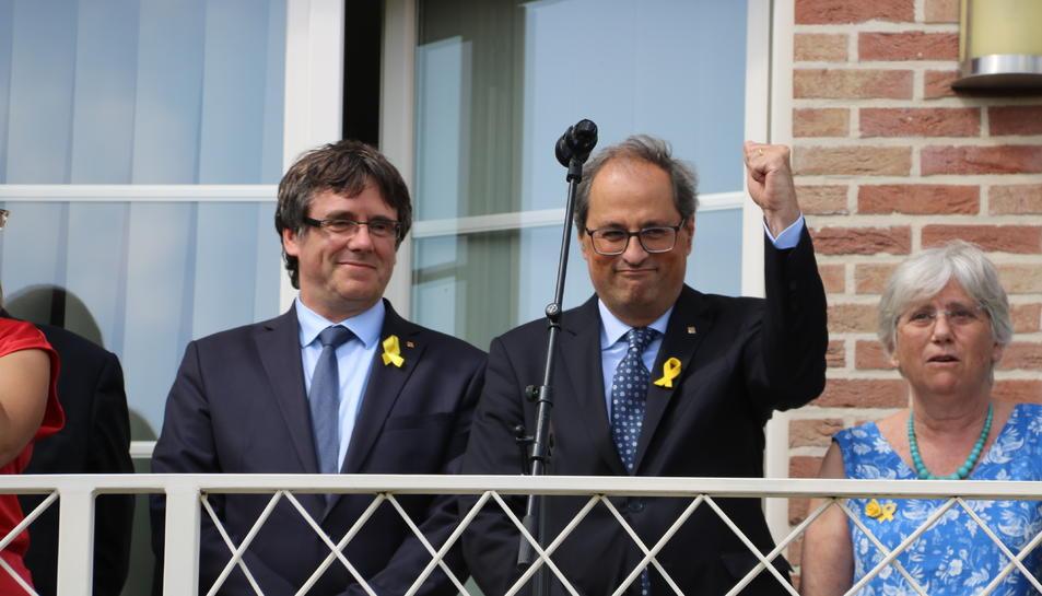 El president Quim Torra aixeca un puny al costat de Puigdemont, en un acte a Waterloo.