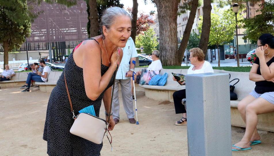 Una dona intentant refrescar-se en una font pública.