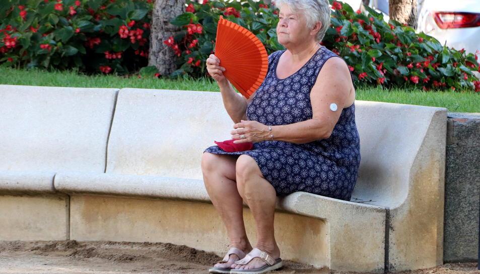 Una dona fent-se vent amb un ventall en una plaça pública de Figueres davant l'onada de calor.