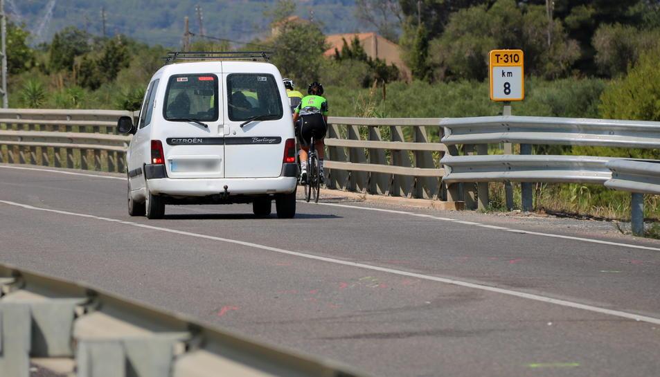 Pla general del punt quilomètric 8 de la T-310 entre Riudoms i Montbrió, amb un grup de ciclistes circulant mentre un cotxe els intenta avançar hores després d'un accident mortal amb dos ciclistes en el mateix punt.