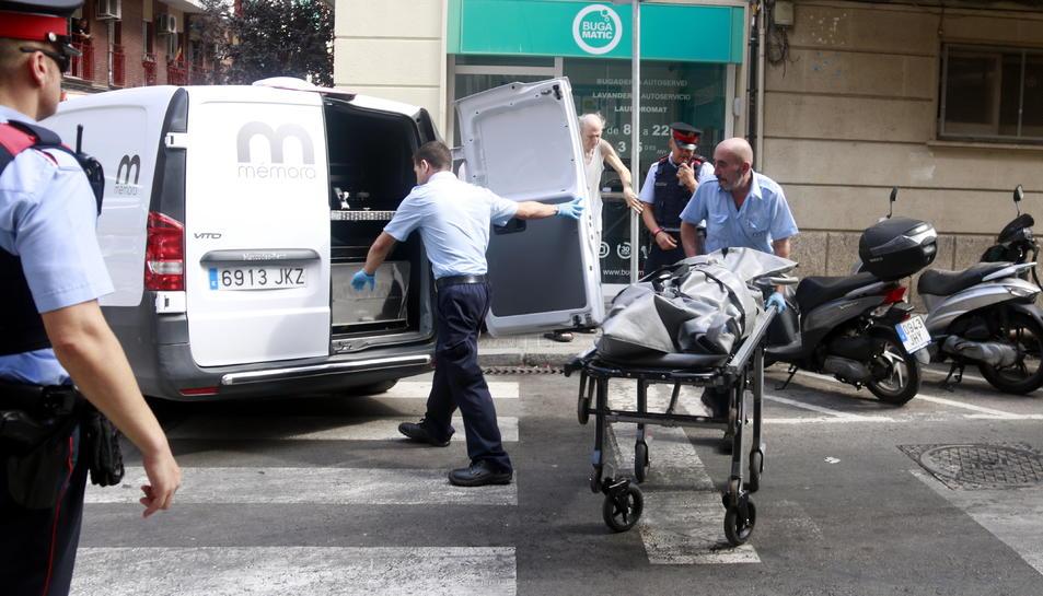 Els serveis funeraris s'enduen el cos de la víctima.