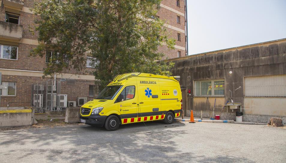 Imatge d'ahir al migdia de l'ambulància amb base a l'hospital Joan XXIII aparcada sota un arbre.