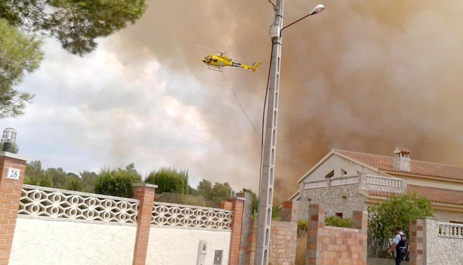 Imatge d'un helicòpter dels bombers sobrevolant la zona al costat de la urbanització.