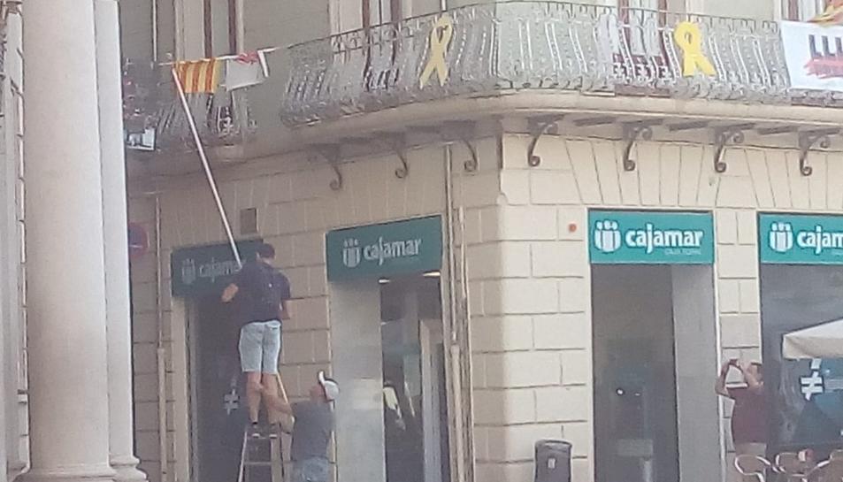 Imatge dels individus traient la pancarta sobre els presos polítics de l'Ajuntament de Reus.