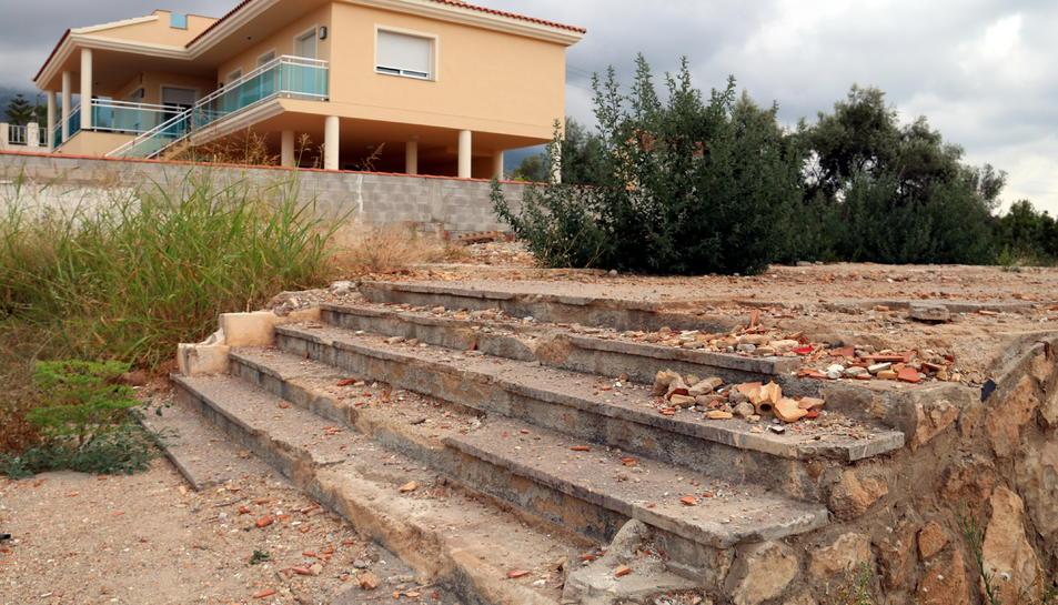 Primer pla de les escales que es van salvar de l'explosió i el solar cimentat que ha quedat on hi havia el xalet dels terroristes del 17-A, amb la casa dels veïns més propera reformada al fons.