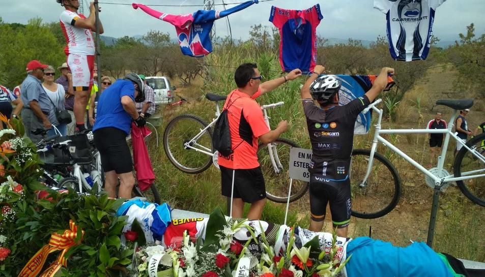 Els ciclistes penjant mallots en record de les dues víctimes just on van perdre la vida