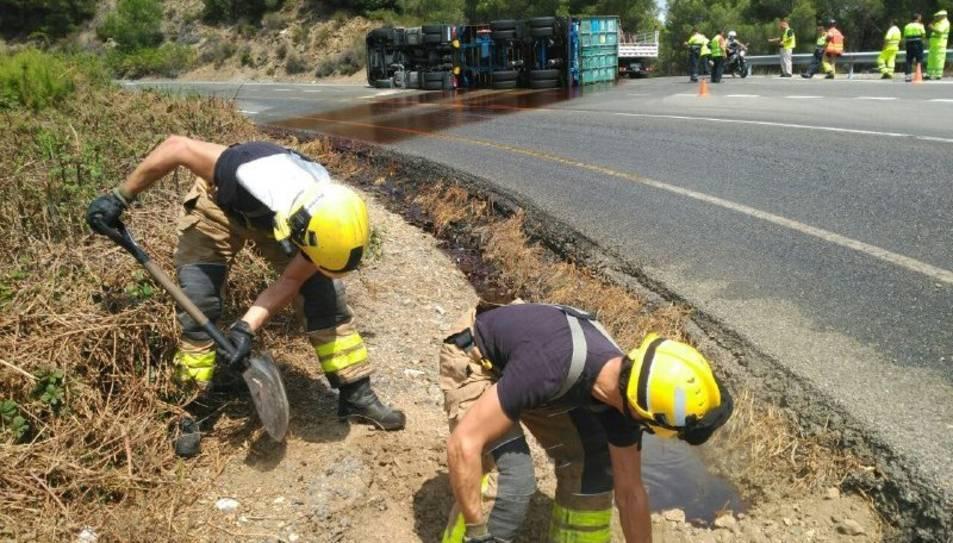 Els Bombers treballant per la fuita d'oli del camió bolcat.