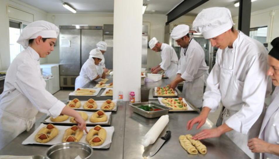 Imatge d'arxiu l'IObrador de l'Escola d'Hoteleria de les Terres de l'Ebre amb els alumnes i professors elaborant mones tradicionals de rosca i ous durs.