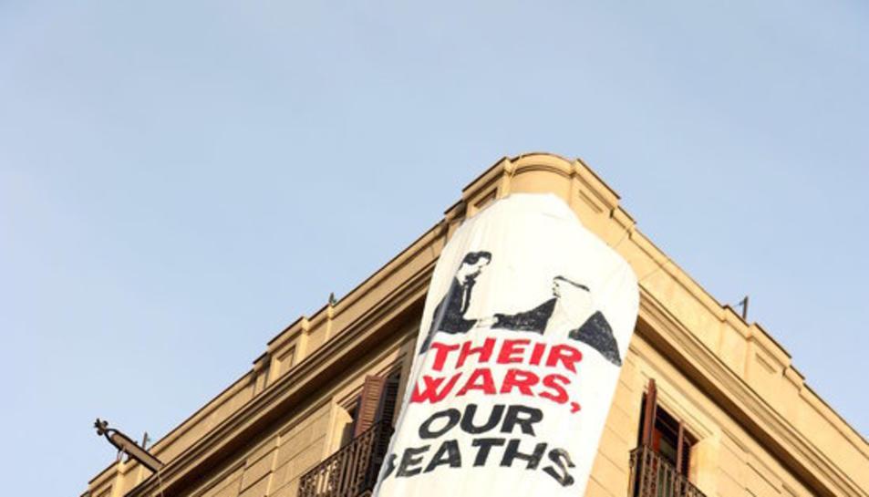 Una pancarta despenjada al Pla de l'Ós, davant el mosaic de Miró de la Rambla, resa: «Les seves guerres, els nostres morts. Catalunya en solidaritat amb les víctimes».